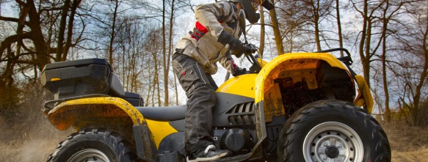 Horizontal motion portrait of a man in gray sport jacket and safety helmet and goggles driving mud-covered yellow ATV 4x4 quad bike with dirt spinning of the wheels photo